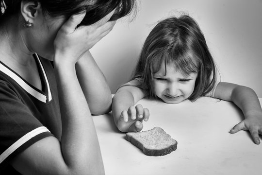 A depressed mother and a hungry daughter pulling her hand to a piece of bread. families with low incomes. crisis