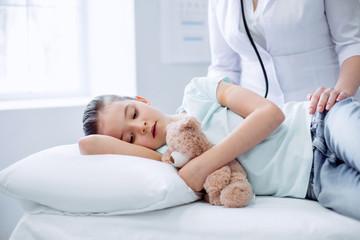 So bad. Nice upset little girl lying while feeling pain and hugging plush bear