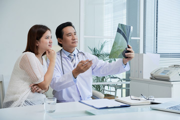 Confident middle-aged surgeon sitting at desk and explaining X-ray results to pretty Asian patient, interior o modern office on background
