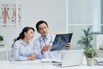 Handsome middle-aged surgeon sitting at desk and showing X-ray image to senior patient while discussing possible treatment, interior of modern office on background