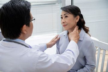 Confident middle-aged doctor wearing eyeglasses examining glands of senior patient while having appointment at modern office