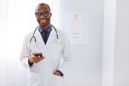 Message from wife. Joyful happy male doctor holding phone while wearing uniform and staring at camera