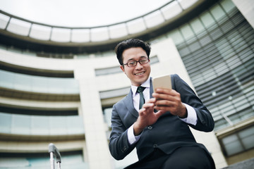 Smiling Asian businessman in eyeglasses texting on smartphone in airport