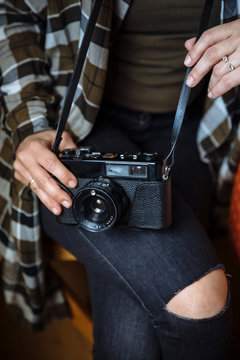 Mid section of woman holding vintage photo camera