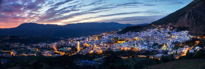 Panorama night city of Chefchaouen Morocco. Blue city in night lights. Journey through Morocco, magical place. Sunset over Chefchaouen, Morocco. Panoramic view of the city