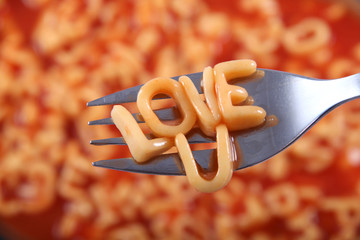 'Love U' written in spaghetti pasta letters for a special message for Valentines Day.