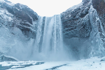 beautiful view of scenic Skgafoss waterfall and snow-covered rocks in iceland