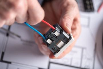Electrician connecting a wire into a power socket