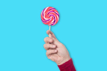 Right female hand holds colorful lollipop upright isolated on pastel light blue background - concept lollipop sweets sugar health tast food kids family fun