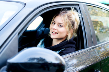 Cheerful girl driving her new car ready to go
