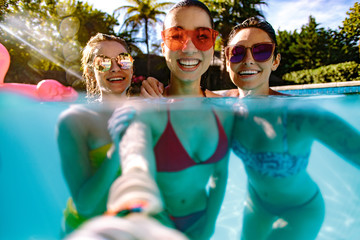 Joyful friends making selfie in swimming pool
