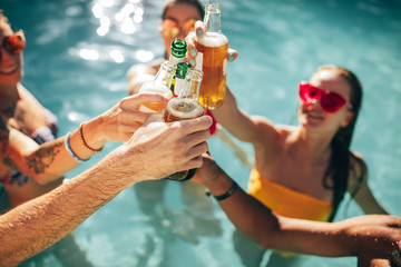 Friends at pool party having beers