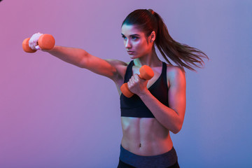 Serious young sports woman make exercises with dumbbells