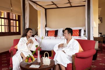 Happy couple in bathrobes enjoying breakfast in hotel bedroom during honeymoon