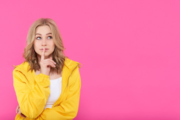 Beautiful trendy girl in colorful clothes deep in thoughts, looking up with finger on lips. Attractive young woman portrait over pastel pink background. Imagination concept.