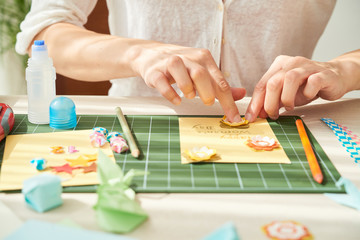 Close-up shot of young woman decorating handmade greeting card for her mother with paper flowers while sitting at wooden table of cozy living room