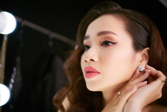 Headshot of beautiful Vietnamese woman sitting at dressing table and putting on earrings while preparing for party in night club