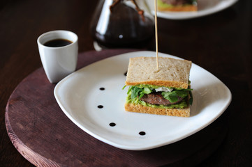 Burger with beef patio and greens in slices of unleavened bread. On white plate with drops of sauce. Coffee on background