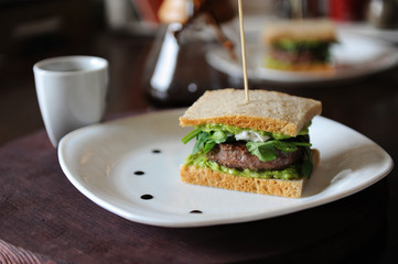 Burger with beef and greens in slices of unleavened bread. On white plate with drops of sauce. Coffee on background