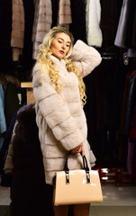 Girl with blonde hair wears fur coat.