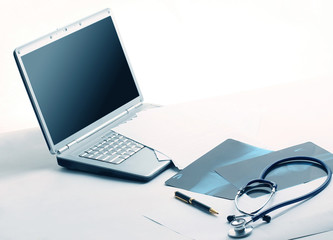 laptop ,stethoscope and x-ray on the table