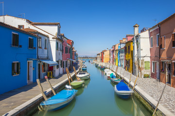 Typical canal with colorful facades with vibrant colors in famous fishermen village on the island of Burano, Venice, Italy