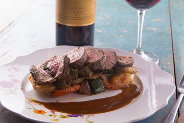 Sliced medium rare steak served with grilled vegetables and red wine on rustic blue wooden table