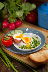 Boiled egg with crunchy bread and healthy vegetables for breakfast
