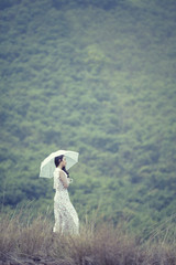 Alone women standing on the hill rock holding white umbrella Vintage.