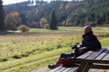Senior man with camera resting on bench looking at nature