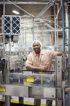 A portrait of an African American worker wearing a head net next to a conveyor belt of lemon flavoured water in a bottling plant.