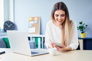 Beautiful smiling woman using phone while working on laptop in home office
