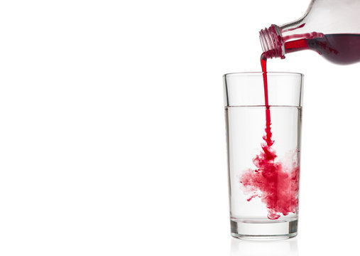 Cranberry syrup pouring into water glass on white background