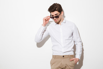 Portrait of sexual masculine man dressed in shirt looking aside from under sunglasses, over white background with shadow