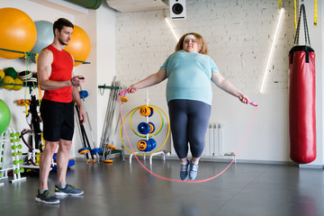 Full length portrait of overweight woman jumping with rope in gym while training with fitness instructor, copy space