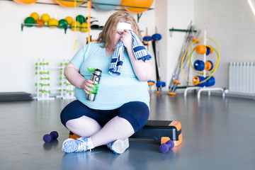 Full length portrait of exhausted obese woman wiping sweat with towel sitting on step after fitness training, copy space