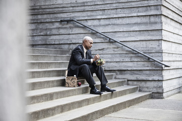Black businessman taking a break for lunch sitting on a stairway step.