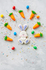 Easter bunny cookies and carrot chewing marmalade with candies on a white stone background. Top view and copy space.