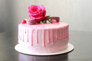 Tasty pink homemade cake decorated by rose and macarons