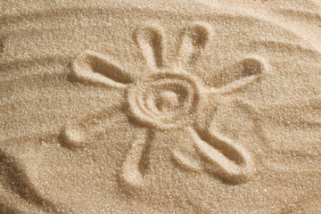 The sun is painted in the sand. Beach background. Top view. The concept of summer, summer kanikkuly, vacation, holydays.