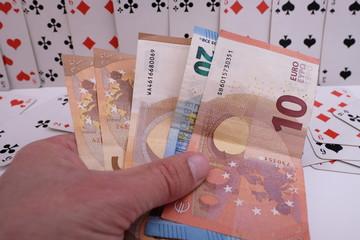 Hand mit Geld mit Spielkarten im Hintergrund