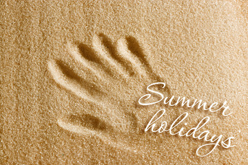 A handprint is drawn on the sand and an inscription of summer holidays. Beach background. View from above. The concept of summer, summer kanikkuly, vacation, holydays.