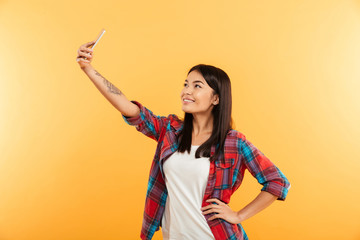 Portrait of a smiling young asian girl taking selfie