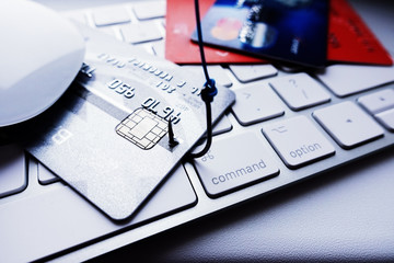 Credit card phishing attack concept, stealing credit card details with fishing hook on laptop keyboard