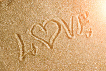 The word love is painted in the sand. Beach background. Top view. The concept of summer, summer kanikkuly, vacation, holydays.