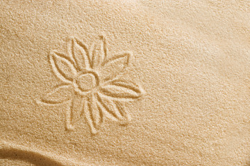 The flower is painted in the sand. Beach background. Top view. The concept of summer, summer kanikkuly, vacation, holydays.