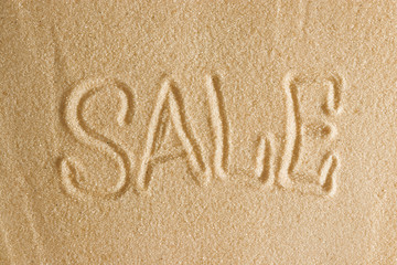 The word sale is painted in the sand. Beach background. Top view. The concept of summer, summer kanikkuly, vacation, holydays.