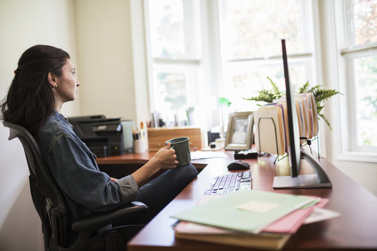 Woman working on a desktop computer in her home office.
