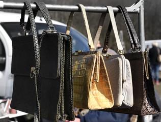 Auf einer Stange hängende Handtaschen auf einem Flohmarkt