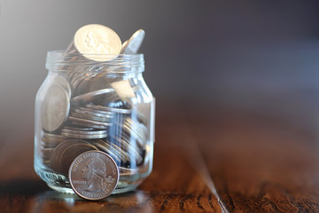 Coins in a glass jar on a wooden floor. Pocket savings from coin
